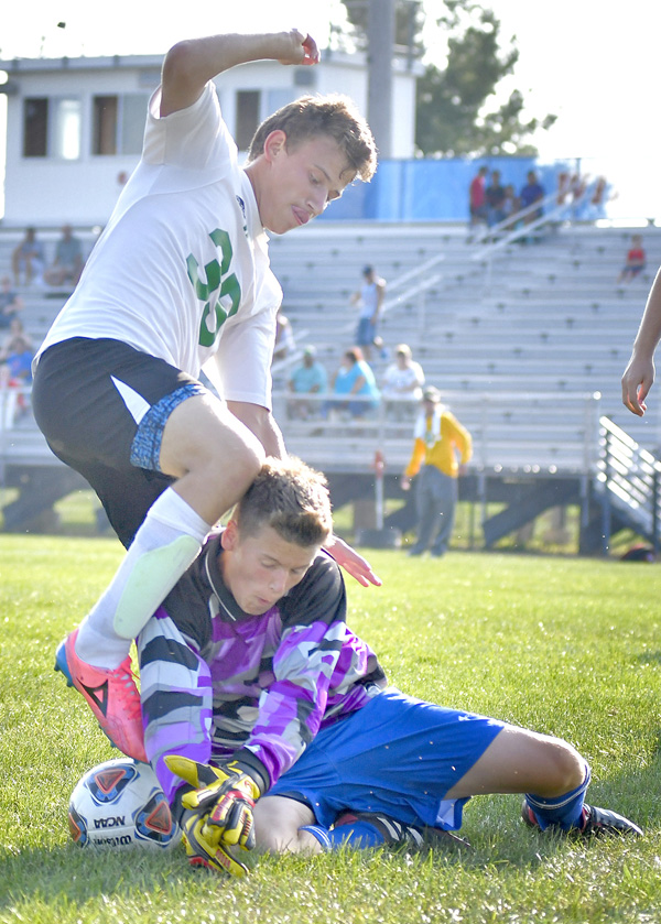 Whitko freshman goalie Austin Kreps makes a save as Tippecanoe Valley's Harrison Vining tries to free the ball. Photo by Gary Nieter, Times-Union