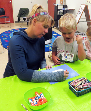 James Swain gets a little help with his craft from Mandy during Preschool Story Time at North Webster Community Public Library.