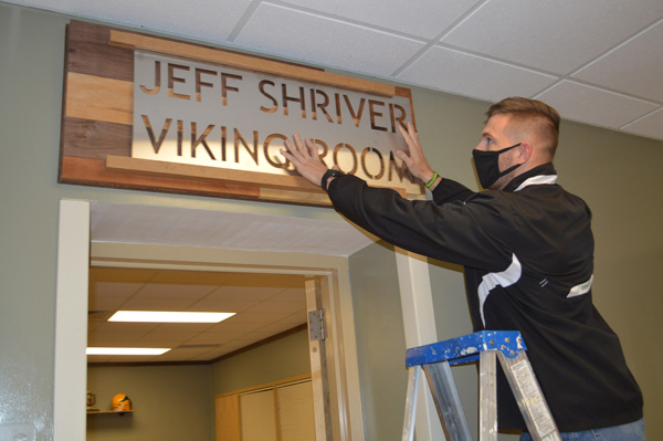Ben Shriver, son of Jeff Shriver, slides the metal name plate into place during the dedication. Photo by Jackie Gorski, Times-Union.
