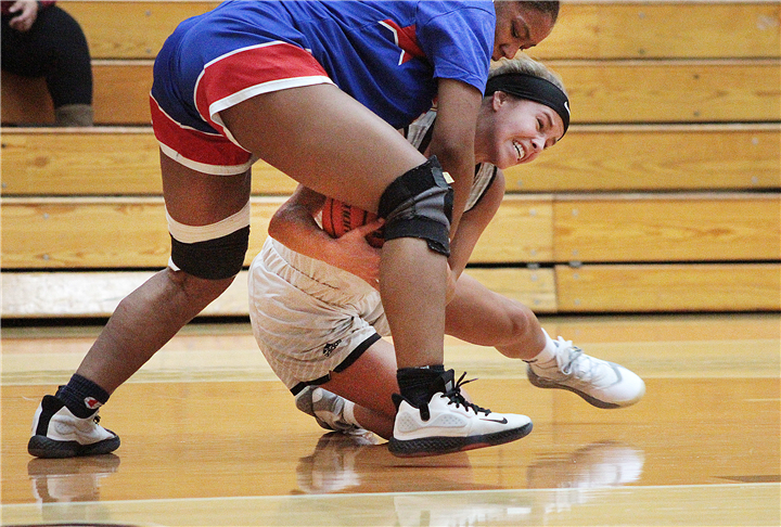 Photo by Drew Fritz, Times-Union Warsaw senior Kendall Wayne fights to take the ball away from a John Adams Lady Eagle during the Lady Tigers' second game of the day on Saturday.