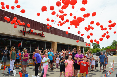 At noon Saturday around the world, red balloons were released into the air to bring awareness to Juvenile Myositis. In Warsaw, 150 were released at Dorothy's Hallmark/Party Shop. Photo by David Slone, Times-Union